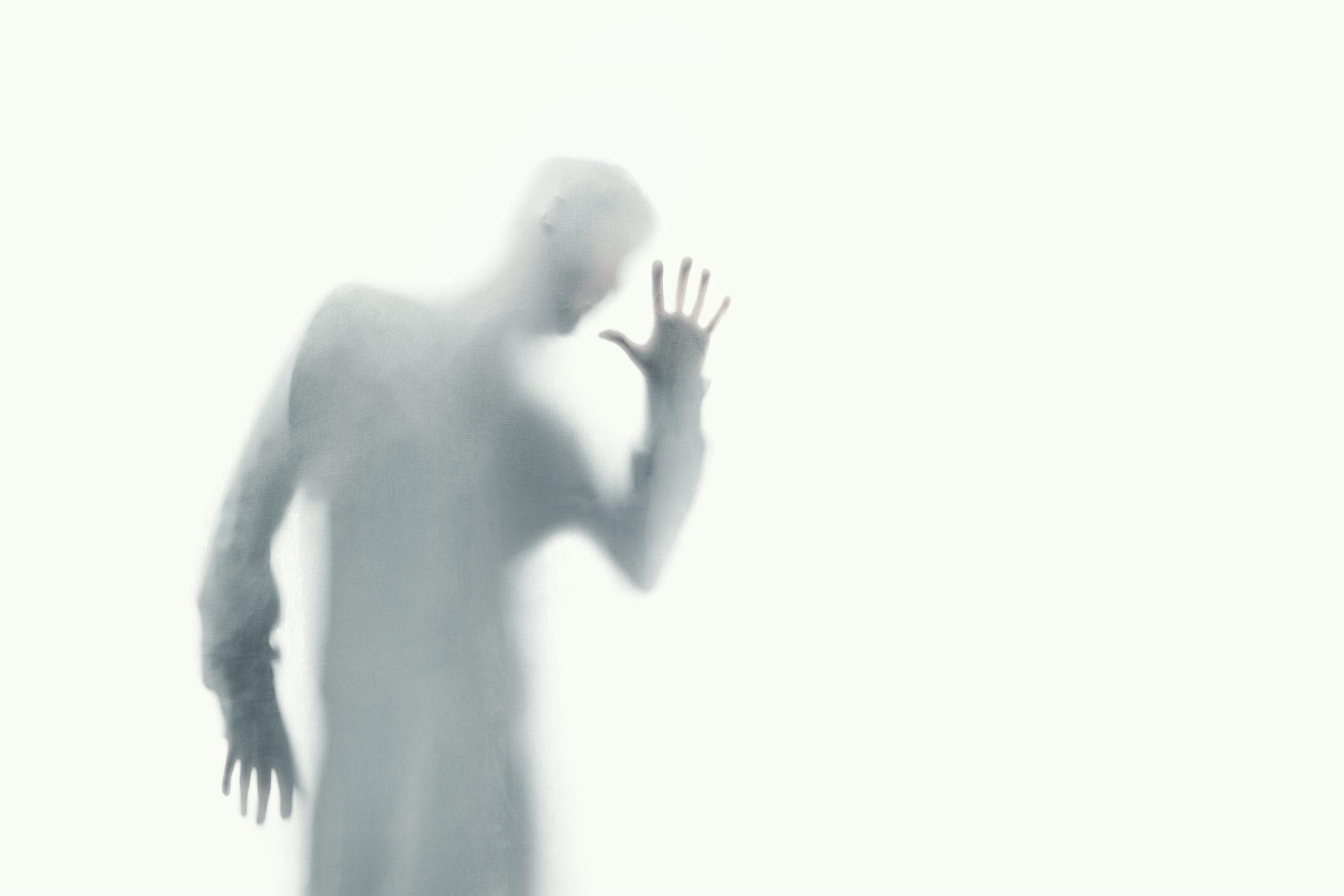 Image d'une figure humaine derrière in rideau